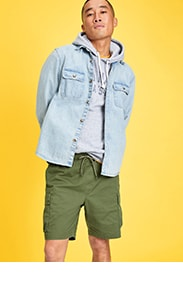 A model is dressed in a grey hoodie with a jean button down over it and army green above the knee shorts.