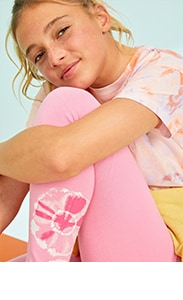 A model wearing a pink tie-dye short sleeve top paired with light pink leggings.
