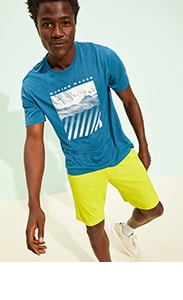 A model wearing a bold blue activewear top paired with bright yellow running shorts.